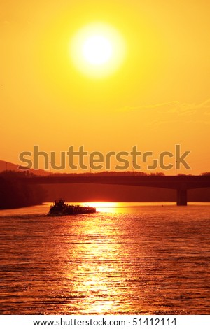 push boat with cargo sailing towards beautiful sunset on the river - stock photo