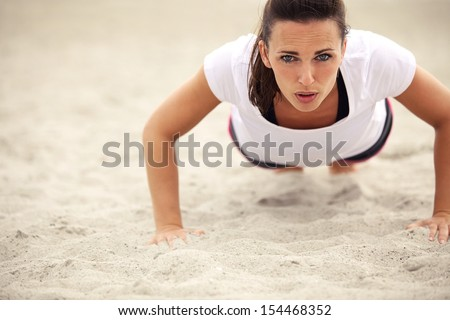 Push-ups fitness woman doing pushups outside on beach. Fit female sport model girl training crossfit outdoors. Caucasian athlete in her 20s. - stock photo