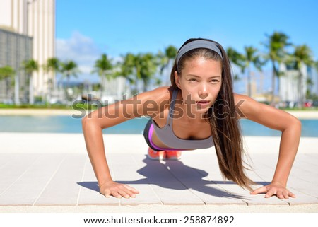 Push-ups fitness woman doing pushups toning arms outside on beachwalk. Fit female sport model girl training crossfit exercise outdoors. Mixed race Asian Caucasian sport athlete in her 20s. - stock photo