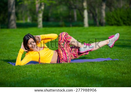 Push ups or press ups exercise by young woman. Girl working out on grass crossfit strength training in the glow of the morning sun against a white sky with copyspace. Mixed race Asian Caucasian model. - stock photo