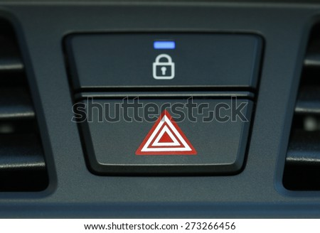pushed red warning button with triangle pictogram, close up view and flasher light - stock photo