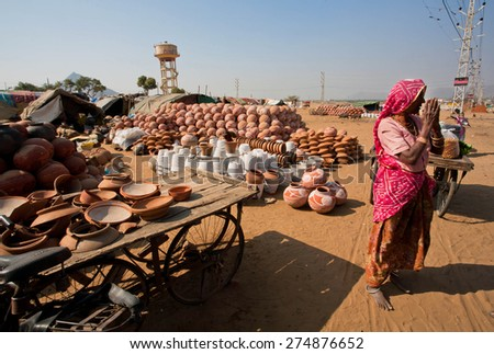 PUSHKAR, INDIA - FEB 9: Senior woman in sari takes hands together in sign Namaste in the village on Fabruary 9, 2015. With population of 15,000 people, Pushkar is an indian town in Ajmer district - stock photo