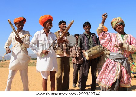PUSHKAR, INDIA - FEB 5: Unidentified nomads play ravanahatha and dance in the deserts on February 05, 2015 in Pushkar, India. Ravanahatha is an ancient instrument used by folk singers in India. - stock photo