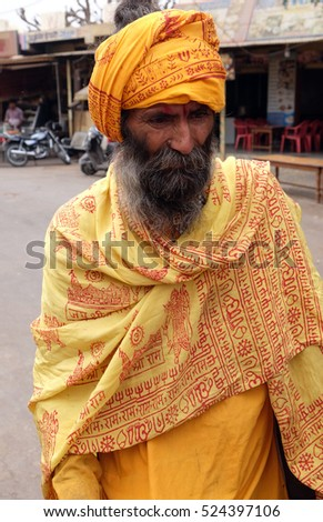 PUSHKAR, INDIA - FEBRUARY 17: An unidentified Indian sadhu holy man walking at the bazaar and collect alms in Pushkar, India on February 17, 2016.