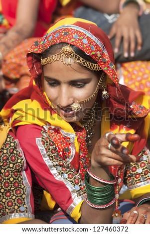 PUSHKAR, INDIA - NOVEMBER 21:  An unidentified girl in colorful ethnic attire attends at the Pushkar fair on November 21, 2012 in Pushkar, Rajasthan, India. - stock photo