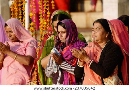 PUSHKAR, INDIA - NOVEMBER 12:Unidentified senior and young women in bright sari perform puja during sunset, at Sarovar lake on November 12, 2013 in Pushkar, India.It's famous place of worship in India - stock photo