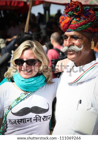 PUSHKAR, INDIA - NOVEMBER 18: Unidentified tourist with moustached man at the Pushkar fair.   Pilgrims and  traders flock to the holy town for the annual fair.  November 18, 2010 in Pushkar,  India