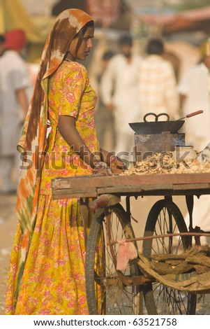 PUSHKAR, INDIA - NOVEMBER 9: Unknown indian woman selling roasted nuts from a cart on November 9, 2008 at the annual camel fair in Pushkar, Rajasthan, India. - stock photo