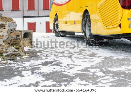 Put chains on the wheels of a bus in order to be able to run on the road is covered with snow in winter.