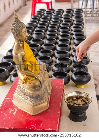 Put coin into small alms bowl, goodness belief in Buddhist religion - stock photo