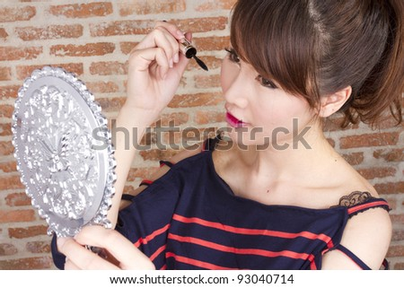 put on make up, female model using black mascara with eyelash.