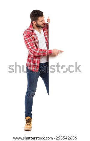 Put something on this white copy space. Handsome young man in jeans and lumberjack shirt standing behind white banner and pointing. Full length studio shot isolated on white. - stock photo
