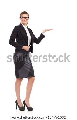 Put your product here. Cheerful businesswoman in black suit raising hand ans showing product. Full length studio shot isolated on white. - stock photo