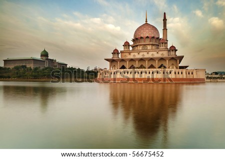 Putra Mosque is the principal mosque of Putrajaya, Malaysia. Building on the left is Perdana Putra which is Malaysian Prime Minister's office. - stock photo