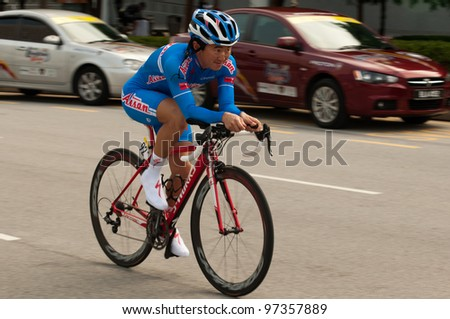 PUTRAJAYA, MALAYSIA - FEBRUARY 24: An unidentified cyclist participates in Stage 1 of the Putrajaya Individual Time Trial for the 2012 Le Tour de Langkawi on Feb. 24, 2012 in Putrajaya, Malays - stock photo
