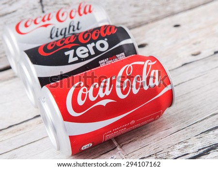 PUTRAJAYA, MALAYSIA - JULY 5TH, 2015. Coca Cola cans on aged wooden background. Coca Cola drinks are produced and manufactured by The Coca-Cola Company, an American multinational beverage corporation.