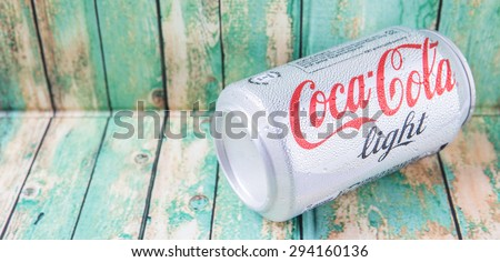 PUTRAJAYA, MALAYSIA - JULY 5TH, 2015. Coca Cola Light on weathered wood. Coca Cola drinks are produced and manufactured by The Coca-Cola Company, an American multinational beverage corporation.