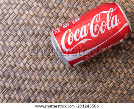 PUTRAJAYA, MALAYSIA - JUNE 28TH, 2015. Coca Cola can on wicker background. Coca Cola drinks are produced and manufactured by The Coca-Cola Company, an American multinational beverage corporation.