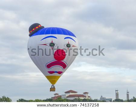 PUTRAJAYA, MALAYSIA-MAR 19:Clown face balloon from Belgium in flight at the 3rd Putrajaya International Hot Air Balloon Fiesta Mar 19, 2011 in Putrajaya.27 International balloonist in this year event - stock photo