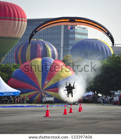 PUTRAJAYA, MALAYSIA - MARCH 30:A paramotor pilot demonstrates his flying skills during 5th Putrajaya International Hot Air Balloon Fiesta at Presint 2, Putrajaya on March 30, 2013. - stock photo