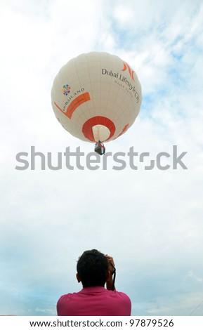 PUTRAJAYA, MALAYSIA-MARCH 15:Dubai Lifestyle City balloon in flight at the 4th Putrajaya International Hot Air Balloon Fiesta March 15, 2012 in Putrajaya.More than 300,000 people visit this event. - stock photo