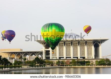 PUTRAJAYA, MALAYSIA-MARCH 18: Hot air balloons in various designs flying over Sultan Mizan Zainal Abidin mosque at the 4th Putrajaya International Hot Air Balloon Fiesta on March 18, 2012 in Putrajaya, Malaysia. - stock photo