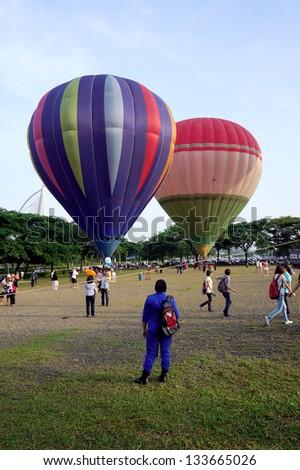 PUTRAJAYA,MALAYSIA- MARCH 29: Tethered hot air balloon rides for visitors at the 5th Putrajaya International Hot Air Balloon Fiesta March 29, 2013 in Putrajaya. - stock photo