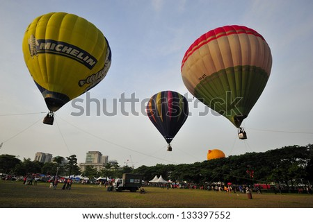 PUTRAJAYA, MALAYSIA - MARCH 30:Three tethered hot air balloons float on the air during 5th Putrajaya International Hot Air Balloon Fiesta at Putrajaya on March 30, 2013. - stock photo