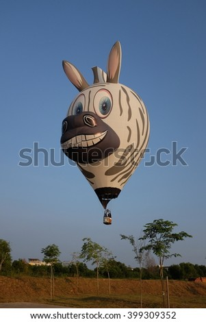 PUTRAJAYA, MALAYSIA - MARCH 12: Zebra shaped hot air balloon floats over sunrise skies at the 8th Putrajaya International Hot Air Balloon Fiesta in Putrajaya, Malaysia on March 12, 2016. - stock photo