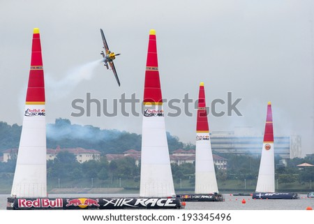 PUTRAJAYA, MALAYSIA - MAY 17, 2014: Peter Busenyei of Hungary, in a Corvus Racer 540 V2 plane flies past the pylons at the qualifying session of the Red Bull Air Race World Championship 2014.