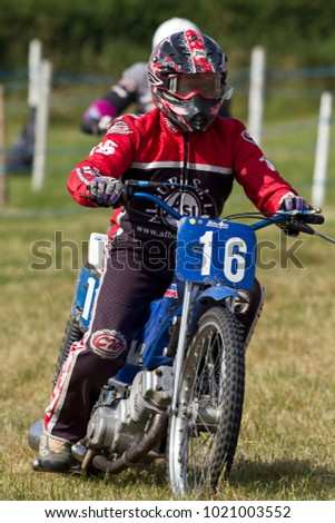 PUTTENHAM, UK - JULY 14: An unnamed rider competing in the Puttenham grasstrack racing event slows down having just crossing the finish line at the end of a heat race on July 14, 2013 in Puttenham