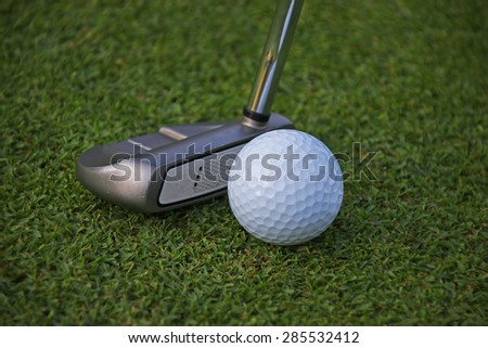Putter and ball on grass prepare to putting
