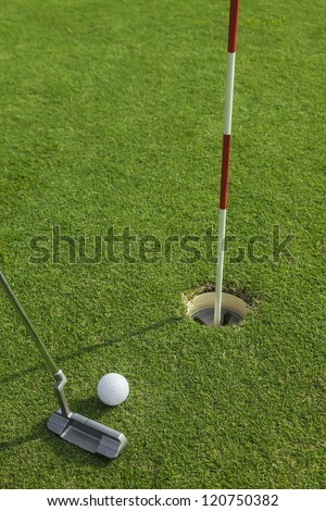 putter puts a golf ball to hole on green of golf course - stock photo