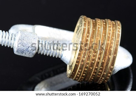 Putting a squeeze on your money - US Currency gold coins in a clamp vise - stock photo