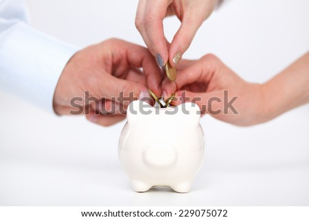 Putting coin into the piggy bank, isolated - stock photo