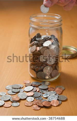 Putting coins in jar, counting spare change on the desktop - stock photo