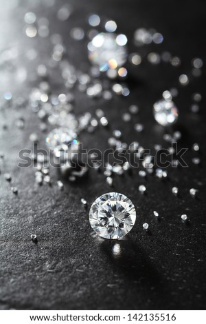putting diamonds on the surface of the stone closeup. more diamonds out of focus in background  - stock photo