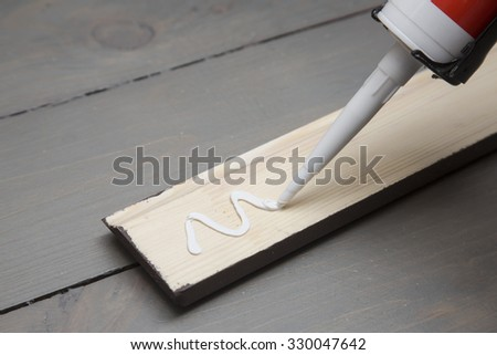 putting glue on a piece of wooden baseboard - stock photo