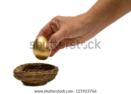Putting Golden Egg In Nest Isolated On White With Small Shadow - stock photo