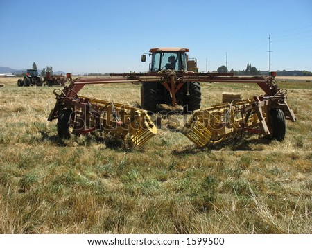 Putting hay in piles for the bailers. - stock photo