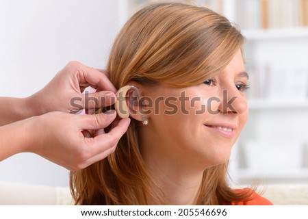 Putting on a deaf aid - stock photo