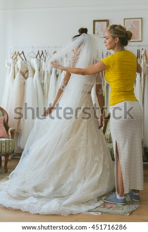 Putting on final touches. Young bride trying on wedding dress with assistant