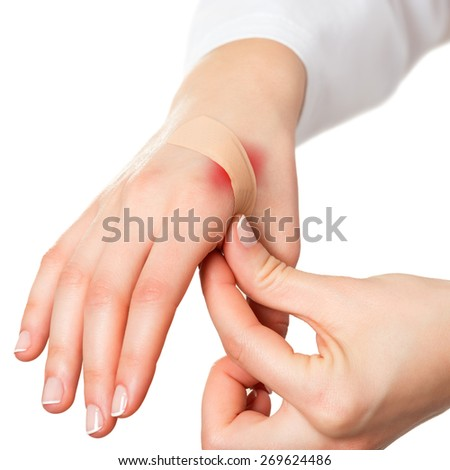 Putting plaster on hurt red skin - stock photo