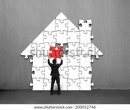 Putting red puzzle into house shape on concrete wall - stock photo