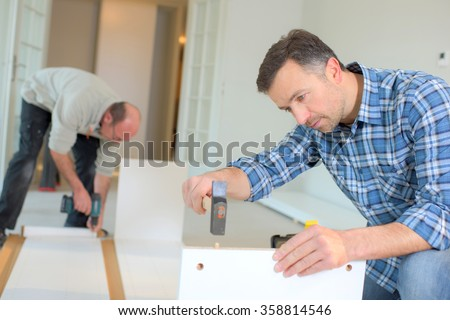 Putting together flap pack furniture - stock photo