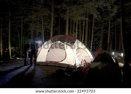 Putting Together Tent at Night on Camp Site - stock photo