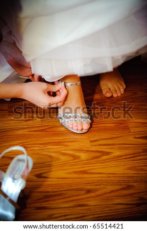 Putting wedding shoes on the bride - stock photo