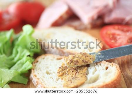 Putting whole-grain mustard on bread to make a ham sandwich - stock photo
