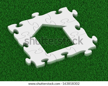 puzzle house on a grass background - stock photo