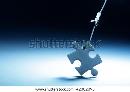 Puzzle on fish-hook - stock photo